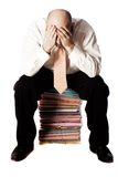 Male Office Worker. Man sitting on pile of files in shirt and tie and head in hands, eyes covered, isolated on white background royalty free stock images
