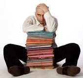 Male Office Worker. Man with hand on top of head, balding, sitting on floor with pile of files between legs stock image