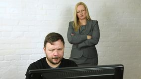 Male office worker at computer with attractive female boss watching over stock footage