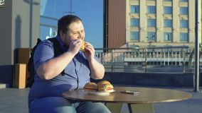 Male office worker eating burger for lunch outdoors, junk food nutrition obesity