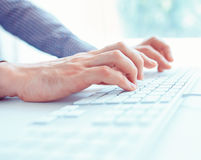 Male office worker typing on the keyboard. Male hands or man office worker typing on the keyboard Stock Photo