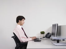 Male Office Worker Using Computer At Desk Royalty Free Stock Photo