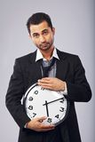 Male Office Worker with a Wall Clock Stock Photo
