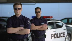 Male officers in sunglasses standing with hands crossed against police car stock video
