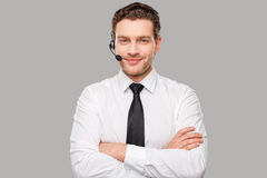Male operator. Handsome young man in formalwear and headset looking at camera and smiling while standing against grey background Stock Image