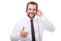 Male operator makes a gesture with his thumb up. Male operator with headset makes a gesture with his thumb up Royalty Free Stock Photo