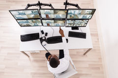 Male Operator Pointing At CCTV Footage On Computer. High Angle View Of Male Operator Pointing At CCTV Footage On Computer Stock Photography