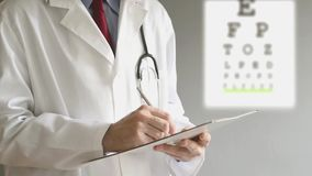 Male ophthalmologist doctor writing prescription after eye examination. stock footage
