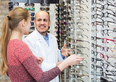 Male ophthalmologist and female patient in modern optics storev Royalty Free Stock Image