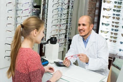 Male ophthalmologist and female patient in modern optics storev Royalty Free Stock Photography