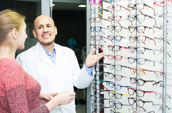Male ophthalmologist and female patient in modern optics storev Stock Image