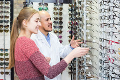 Male ophthalmologist and female patient in modern optics storev Royalty Free Stock Photo