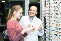 Male ophthalmologist and female patient in modern optics storev Royalty Free Stock Images