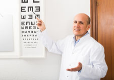 Male ophthalmologist pointing at letters. Elderly male ophthalmologist pointing at letters of eye chart stock photos