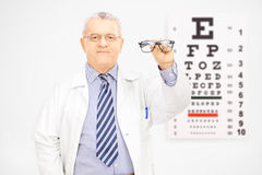 Male optician holding glasses in front of an eye chart Royalty Free Stock Images