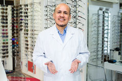 Male optician near stand with glasses. Friendly smiling male optician posing near stand with spectacles and instruments Stock Photos