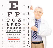 Male optician pointing to an eyesight test with a stick Royalty Free Stock Photos