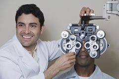Male Optometrist Adjusting Panels Of Phoropter Stock Photos