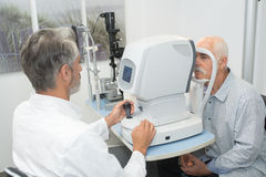 Male optometrist doing sight testing for old patient stock photo