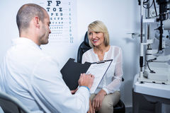 Male optometrist talking to female patient Royalty Free Stock Image