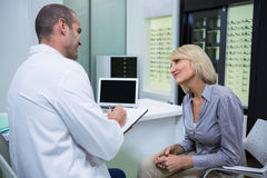 Male optometrist talking to female patient Stock Photos
