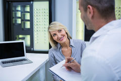Male optometrist talking to female patient Royalty Free Stock Images