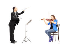 Male orchestra conductor directing a female playing violin. Isolated against white background Royalty Free Stock Images