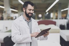 A male orthopedic pose against the background of a large store of beds. He holds tablet in his hands and looks at him. An orthopedic man is posing against a Royalty Free Stock Images
