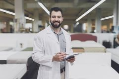 A male orthopedic pose against the background of a large store of beds. He holds tablet in his hands and looks at him. An orthopedic man is posing against a Royalty Free Stock Image