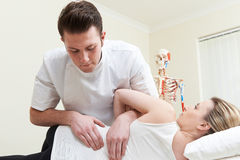 Male Osteopath Treating Female Patient With Back Problem Royalty Free Stock Photos