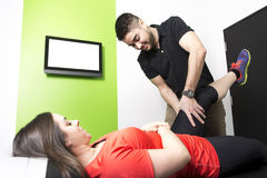 Male Osteopath Treating Female Patient With Hip Problem stock photography