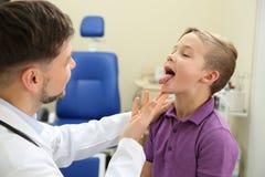 Male otolaryngologist examining little child. In hospital royalty free stock photos