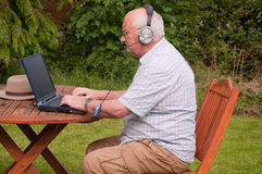 Male outside on laptop. Senior male outside using laptop to make voip call Royalty Free Stock Photo