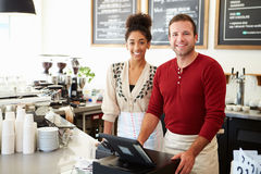 Male Owner Of Coffee Shop. With female assistant stock photography