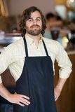 Male Owner With Hands On Hips. Portrait of confident male owner with hands on hips standing in cafeteria stock photo