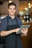 Male Owner Holding Digital Tablet In Cafeteria Royalty Free Stock Image