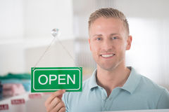 Male Owner Holding Open Sign In Clothing Store. Portrait of confident male owner holding open sign in clothing store Royalty Free Stock Photo