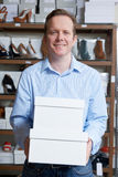 Male Owner Of Shoe Store Carrying Boxes. Owner Of Shoe Store Carrying Boxes Royalty Free Stock Image