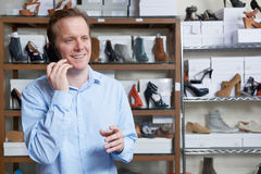 Male Owner Of Shoe Store On Phone. Owner Of Shoe Store On Phone Royalty Free Stock Image