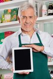 Male Owner Showing Digital Tablet In Store. Portrait of happy senior male owner showing digital tablet in grocery store stock image