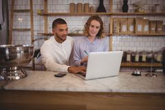 Male owner and young waitress using laptop while sitting at counter Royalty Free Stock Photo