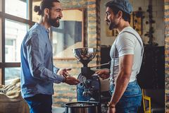 Male owners standing happy by the coffee roaster. Hipster owners standing happy and smiling by the coffee roaster machine royalty free stock image