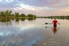 Male paddler with a long stand up paddle. Standing in a calm lake, summer scenery Stock Photography