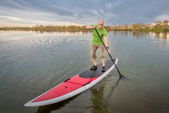 Male paddler on stand up paddleboard. Senior male paddler on a paddleboard, lake in Colorado with a fall scenery and dark clouds Stock Photos