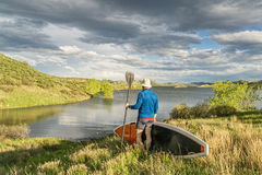 Male paddler with stand up paddleboard. (SUP) on a grassy shore of mountain lake - Horsetooth Reservoir near Fort Collins, Colorado Stock Photo