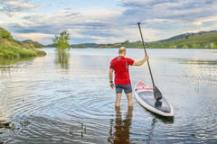 Male paddler with SUP paddleboard on lake Royalty Free Stock Image