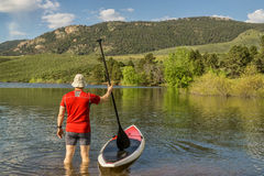 Male paddler with SUP paddleboard on lake Stock Image