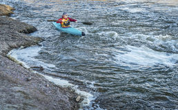Male paddler in a whitewater kayak Royalty Free Stock Images