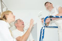 Male painter and apprentices looking at ceiling. Male painter and apprentices looking at the ceiling royalty free stock images