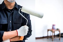 Male Painter with arm crossed holding paint roller, Interior working with paint roller in room, shape and structure royalty free stock image